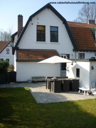 Met zonnige omsloten tuin met gazon, ingegraven trampoline, schommel, bbq, terras, grote eettafel.
