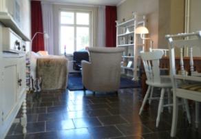 Ruime woonkamer met tv/zithoek en grote houten eettafel