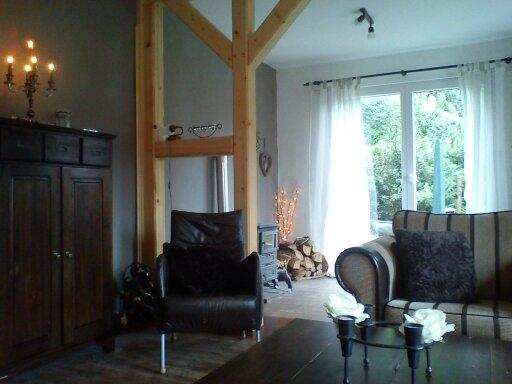 Knusse woonkamer met houtkachel en toegang naar terras